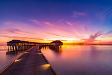 Sunset In Maldives Island. Beautiful Sunset Sky And Clouds, Luxury Water Villas And Wooden Pathway - Pier