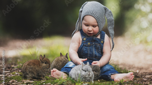 Little child sitting with hares in forest