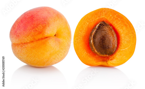 Fresh whole apricot fruit and half isolated on white background