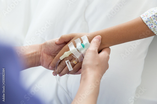 Fotografie, Obraz  Beautiful young nurse preparing  saline solution on bed in rehabilitation room, saline solution drip on hand