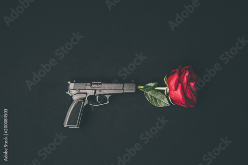 Fotografia Red rose shooting from gun isolated on black