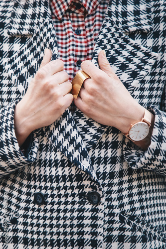 detail shot of a woman outdoors posing in a checked patterned coat, wearing a golden ring and watch and holding a black backpack Canvas Print