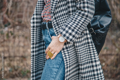 detail shot of a woman outdoors posing in a checked patterned coat, wearing a golden ring and watch and holding a black backpack Wallpaper Mural