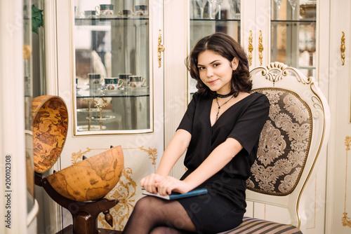 Fotografie, Obraz  Stylish elegant brunette woman in beauty rich interior, wearing black dress