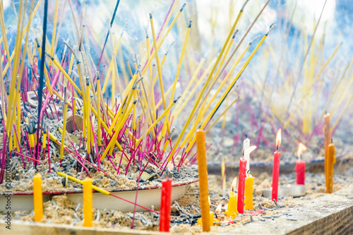 Poster Gris Close-up view of burning incense sticks planted among coins into a pile of sand on a table, diffusing a bluish smoke during a buddhist ceremony, with lighted candles in the foreground.