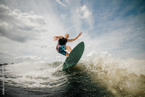 Athletic man wakesurfing on the board against the cloudy sky