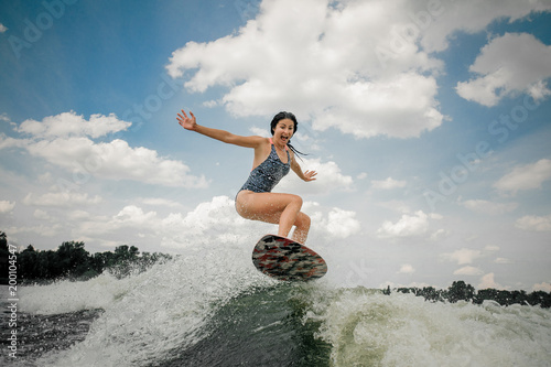 Screaming young woman jumping on the board wakesurfing on the river