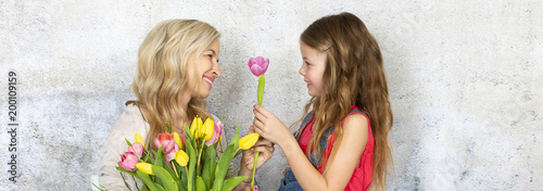 Young and blond and pretty mother gets a bouquet of colorful flowers from her daughter on Mother's Day