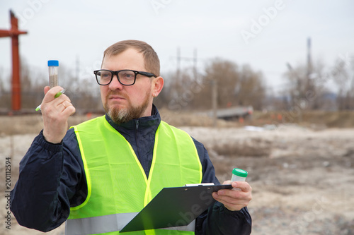 Valokuva  Man ecologist takes samples of soil. Ecological control.