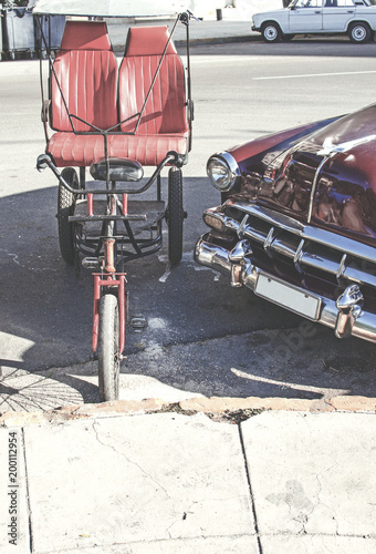Photo different types of transportation in a street of Cuba, a classic car and a bike