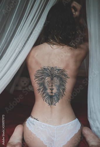 31e7d8441 Naked back with the tattoo of a lion of a young woman sitting on a bed