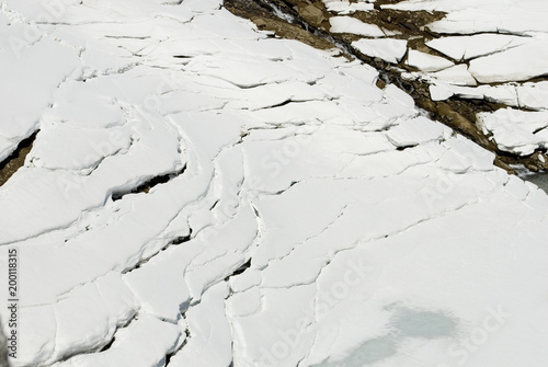 Valokuva  crevasse in the snow and ice, caused by high temperatures, above a frozen lake o