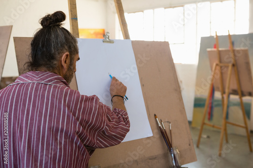 Rear view of man painting on paper