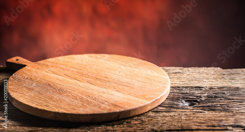 Empty pizza round board  old wooden table and colour blurred background