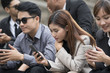 Close up of businessmen and businesswomen using smartphone, business communication concept