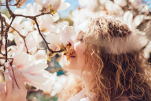 Beautiful Smiling Girl Sniffs Fragrant Magnolia Flowers, Walks In The Park On A Warm Spring Day