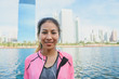Young asian woman relax herself by listening to music after city running exercise with a city view background and warm light cleared sky late of the afternoon. Outdoor running exercise concept.