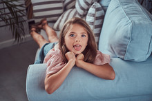 Portrait Of A Happy Little Girl With Long Brown Hair And Piercing Glance, Shows Tongue On The Camera, Lying On A Sofa At Home