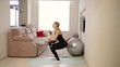 woman strengthens the buttocks muscles during the home exercise, she hold baby
