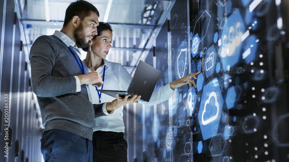 Fototapety, obrazy: Male IT Specialist Holds Laptop and Discusses Work with Female Server Technician. They're Standing in Data Center, Rack Server Cabinet with Cloud Server Icon and Visualisation.