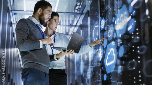 Male IT Specialist Holds Laptop and Discusses Work with Female Server Technician. They're Standing in Data Center, Rack Server Cabinet with Cloud Server Icon and Visualisation.