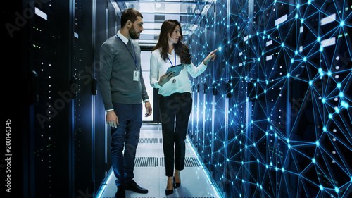 Stampa su Tela  Female and Male IT Engineers Discussing Technical Details in a Working Data Center/ Server Room with Internet Connection Visualisation