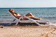 Young woman in a swimsuit wearing sunglasses lies on a deckchair in the sea. Concept life style