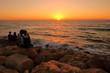 Romantyczny zachód słońca nad morzem, umocnione kamieniami nabrzeże i woda oświetlona złotymi promieniami zachodzącego słońca, przytulona para siedzi tyłem, na kamieniach, wpatruje się w słońce