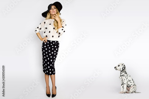 Fotografie, Obraz  Beautiful, sexy blonde woman in elegant polka dots and a hat, standing on a whit