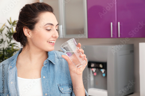Woman with glass of water from cooler in office