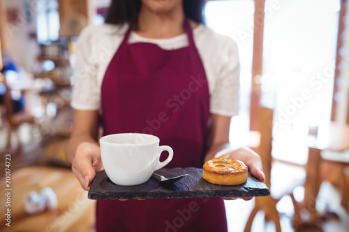 Mid-section of waitress holding a cup of coffee and snacks
