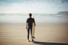 Surfer Standing With Surfboard On Beach