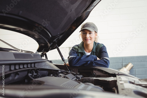 Portrait of female mechanic standing with arms crossed