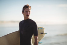 Man Holding Surfboard While St...