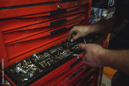 Mechanic removing nuts from tool box