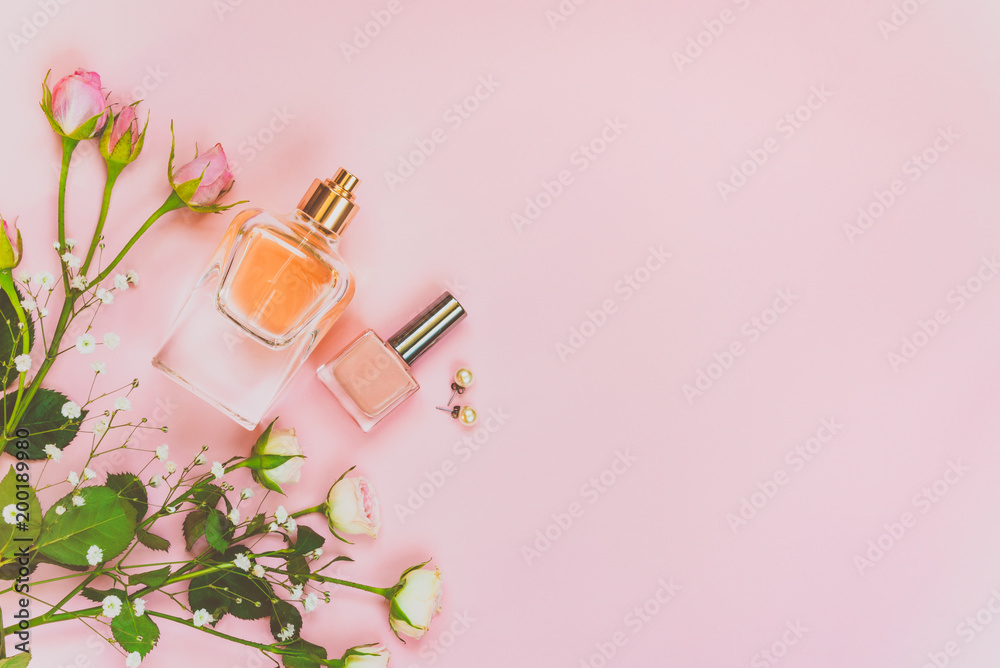 Fototapety, obrazy: Flat lay of female cosmetics products and accessories. A bottle of perfume, nude nail polish, pearl earings and roses over pink background. Copy space.
