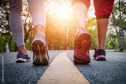 Foto  Women and men runner feet on road in workout wellness concept.