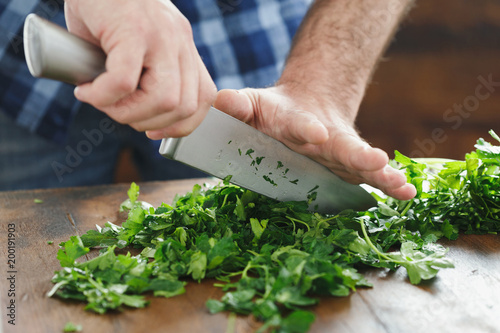 Deurstickers Koken Close up male hands chopping fresh parsley