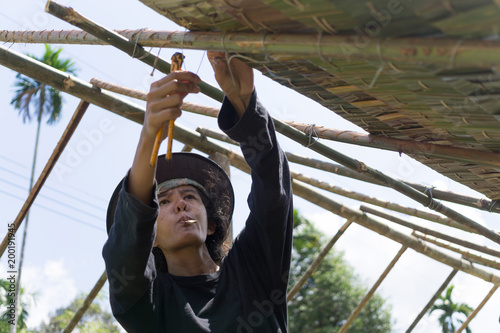 female worker is thatching roof, concept about labor Wallpaper Mural