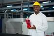 Male worker showing juice bottle in factory