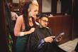 Client showing digital tablet to female barber