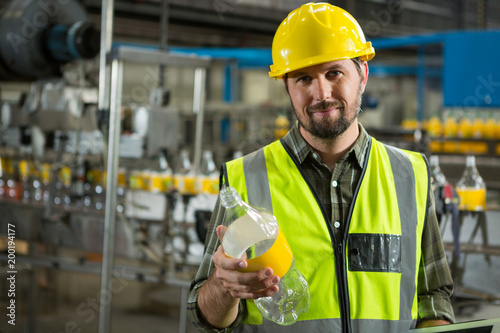 Confident male worker inspecting bottles in juice factory