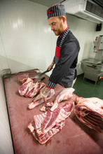 Butcher Cutting The Ribs Of Po...
