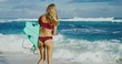 Beautiful young woman at the beach going surfing, surfer beach lifestyle