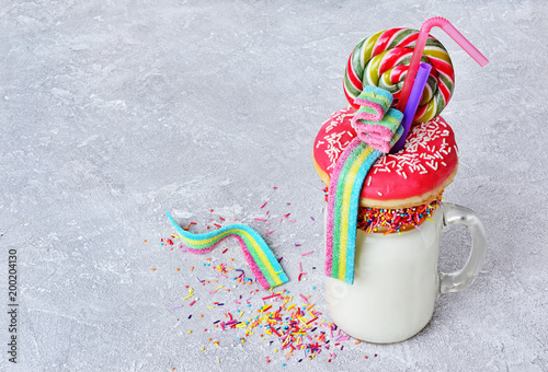 Foto auf AluDibond Milch / Milchshake Crazy milk shake with pink donut, color candy and lollipop in glass jar