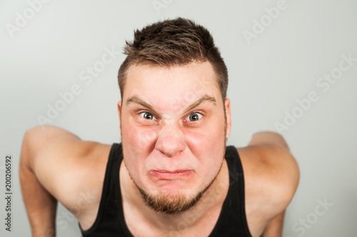 Fotografia, Obraz  Young funny bearded guy dressed in black tank top sitting on the toilet on gray background