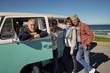 Happy senior people traveling with camper van by the ocean