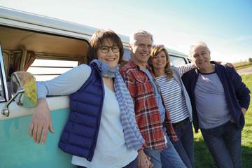 Senior people on a road trip with camper van enjoying stop in countryside