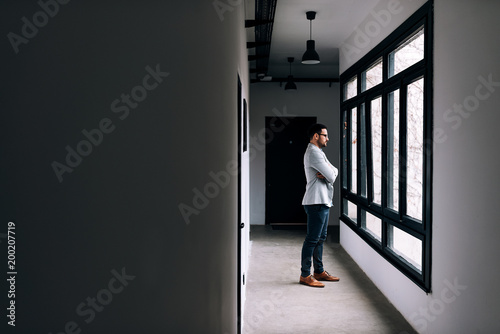 Side view of businessman standing with crossed arms and looking through office building window.