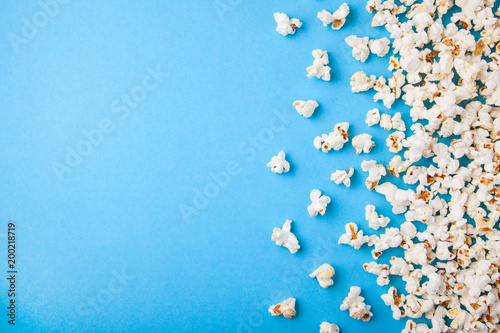 Fotografía  Popcorn scattered on blue background. Copy space for text